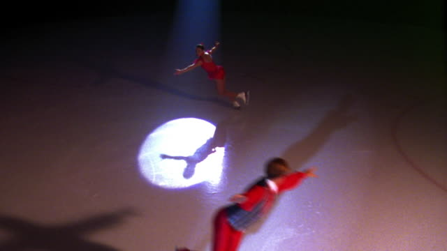 high angle male + female figure skaters with legs out in pose spinning together in spotlight - figure skating stock videos and b-roll footage