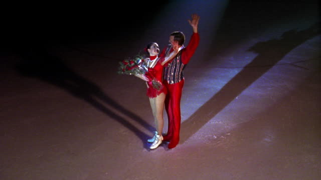 high angle male + female figure skaters with medals + roses standing in spotlight looking around + waving - medallist stock videos & royalty-free footage
