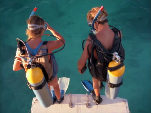 high angle male + female scuba divers jumping into water - schnorchel stock-videos und b-roll-filmmaterial