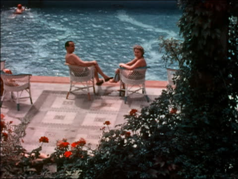 stockvideo's en b-roll-footage met 1938 high angle man and woman sitting by swimming pool at hotel in budapest, hungary - 30 39 jaar