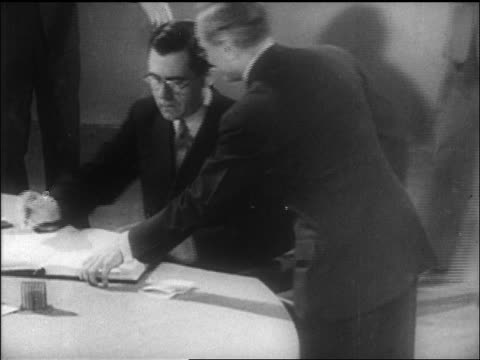 B/W 1946 high angle man assisting Soviet delegate in eyeglasses sign UN charter / SF / newsreel