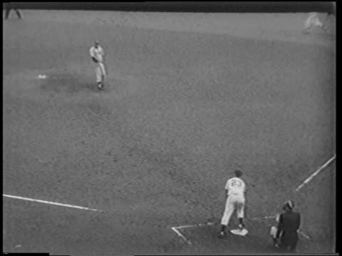 high angle man at bat hitting ball + running / man running from third base to home plate / nyc - 1951点の映像素材/bロール