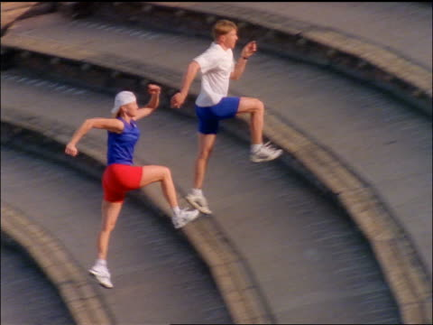 high angle PAN man + blonde woman wearing baseball cap running up stadium steps / Red Rocks Amphitheater