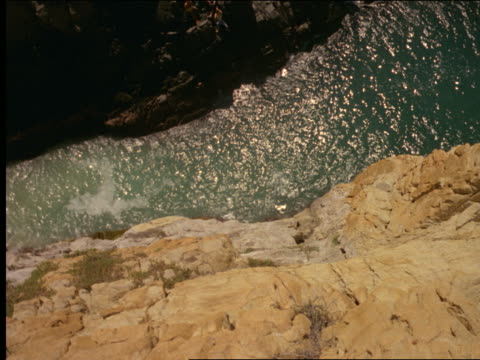 high angle man diving off cliff into water