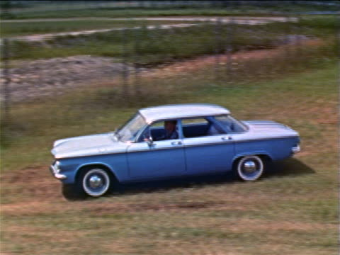 vídeos de stock e filmes b-roll de 1960 high angle pan man driving blue corvair on grass past fence / industrial - general motors