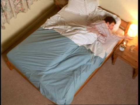 t/l high angle, man gets into bed, goes to sleep, changing body position during night, then gets up - posizione descrittiva video stock e b–roll