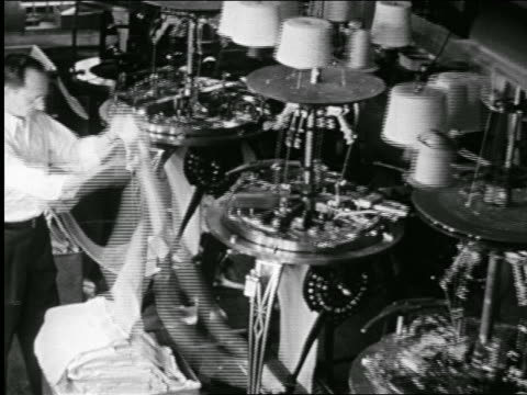 b/w 1946 high angle man guides cloth through bobbins machine at clothes manufacturing plant / docu. - textile industry stock videos & royalty-free footage