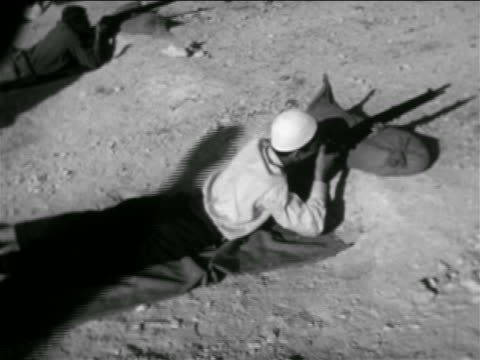 stockvideo's en b-roll-footage met b/w 1957 high angle man lying on ground aiming rifle / syria / newsreel - 1957