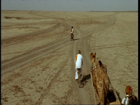 vídeos de stock, filmes e b-roll de wa high angle, man on bike and family on cart moving through desert, gujarat, india - tradição