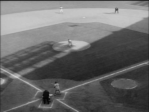 high angle man pitching ball, batter bunting + running to first base, pitcher throws to first - 1955 stock-videos und b-roll-filmmaterial