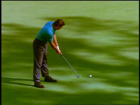 vídeos y material grabado en eventos de stock de high angle pan man putting golf ball toward hole where boy holds flag / ball hits boy's foot + goes in hole - bandera de golf