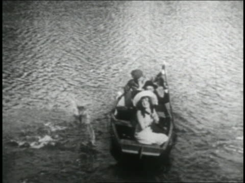 b/w 1916 high angle man rowing boat with man + clapping woman away from camera / feature - 1916 stock videos & royalty-free footage