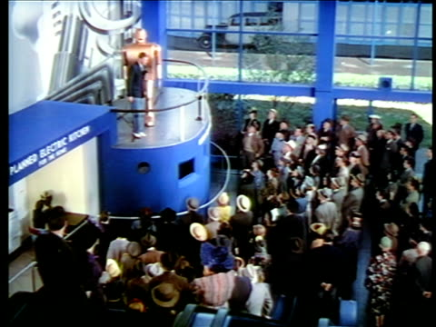vidéos et rushes de 1940 high angle man standing next to large robot talking to crowd below / new york world's fair / industrial - exposition universelle de new york
