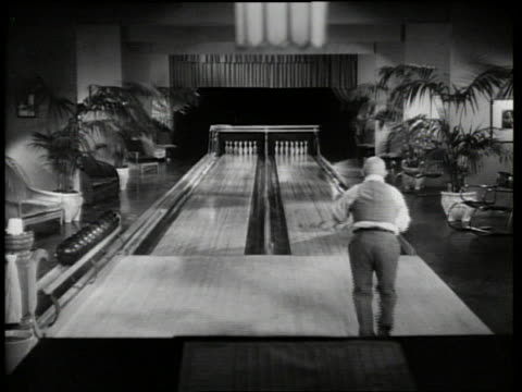 b/w 1934 high angle man throwing bowling ball slides down alley attached to ball / strikes and spares - 1934 stock videos & royalty-free footage