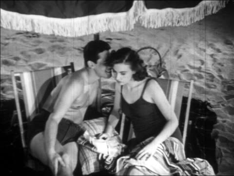 B/W 1936 high angle man with bathing suit whispering to woman with bathing suit under umbrella on beach