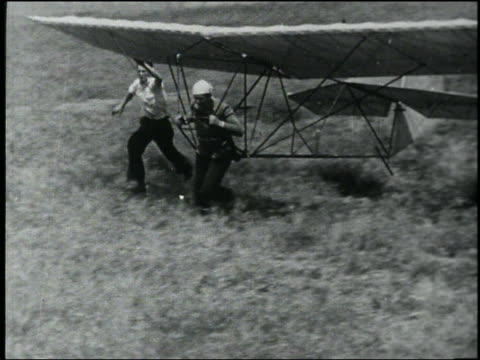 b/w high angle pan man with early hang glider running in field - 発明家点の映像素材/bロール