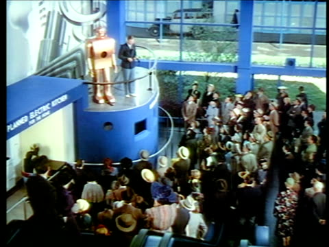 1940 high angle man with robot on platform talking to crowd below / new york world's fair / industrial - l'uomo e la macchina video stock e b–roll