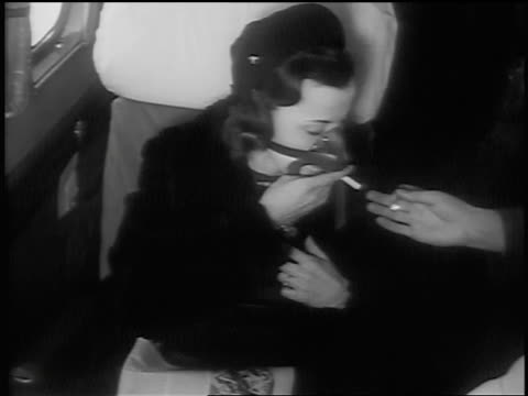 B/W 1939 high angle MS man's hand lighting cigarette with match for woman wearing oxygen mask on airplane
