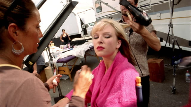 High angle medium shot actress sitting and having makeup applied + hair styled / being presented with dress