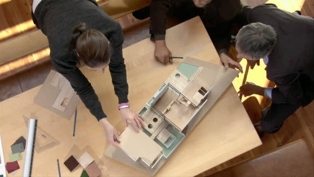 High angle medium shot architects around table working with model