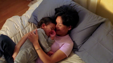 high angle medium shot asian woman and toddler lying together on bed - toddler stock videos & royalty-free footage