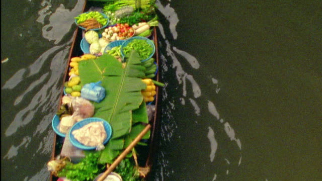 High angle medium shot Asian woman paddling boat filled with food at floating market / Damneon Saduak, Thailand