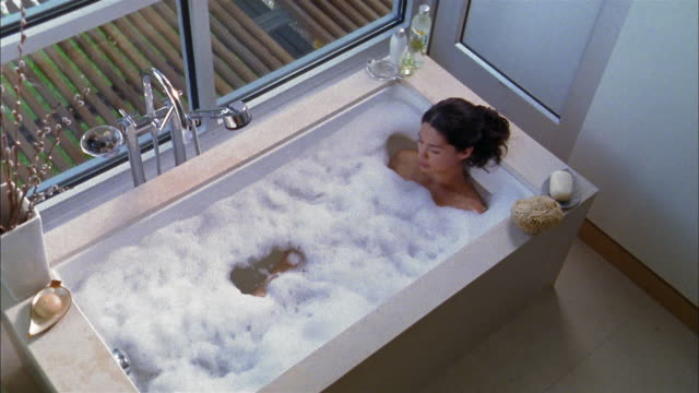 High angle medium shot Asian woman reclining in bubblebath in bathtub