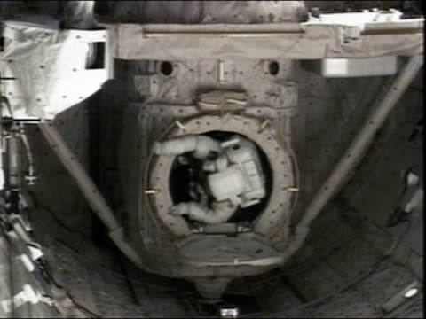 high angle medium shot astronaut climbing out of a hatch on the international space station - portello video stock e b–roll