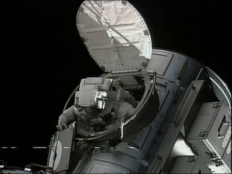high angle medium shot astronaut climbing out of a hatch on the international space station - heckklappe teil eines fahrzeugs stock-videos und b-roll-filmmaterial