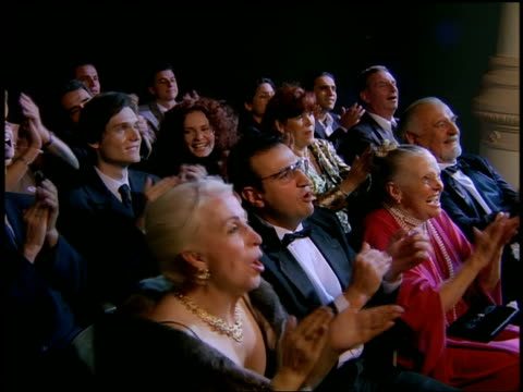 High angle medium shot audience in formalwear clapping at theater (fast motion to normal)