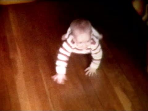 1972 High angle medium shot baby crawling on hardwood floor, grabbing jack-in-the-box