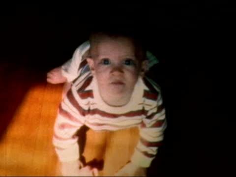 vídeos y material grabado en eventos de stock de 1972 high angle medium shot baby crawling on hardwood floor - babies only