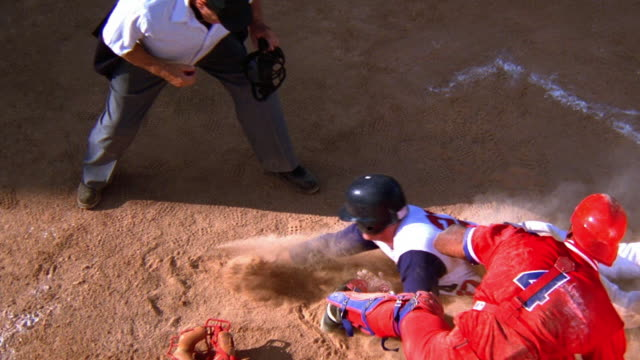 High angle medium shot baseball catcher tagging runner sliding into home plate with umpire signaling out