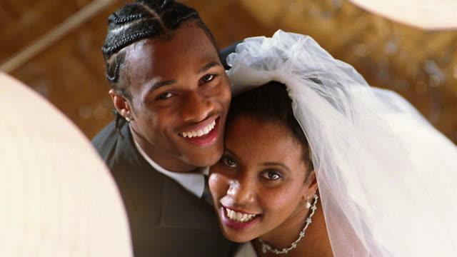 High angle medium shot Black bride and groom posing on dance floor