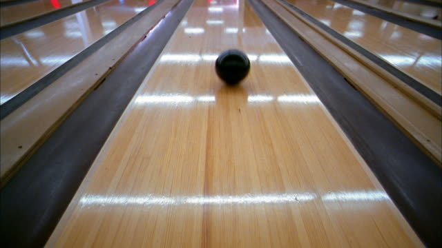 vídeos de stock, filmes e b-roll de high angle medium shot bowling ball rolling down lane - cancha de jogo de boliche