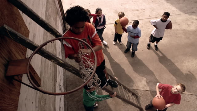High angle medium shot boy attaching net to basketball hoop / kids watching from below