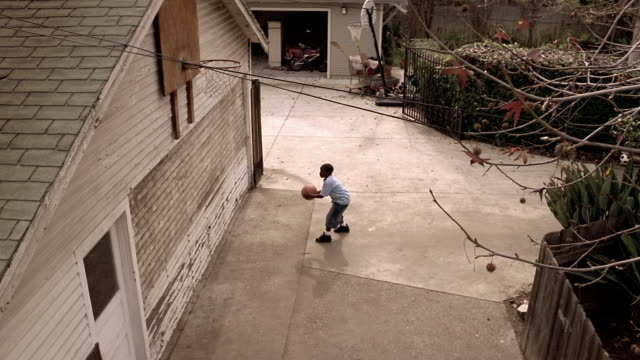 High angle medium shot boy shooting basketball at hoop above garage
