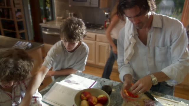 High angle medium shot boys doing homework at kitchen island as man prepares food / woman at kitchen sink in background