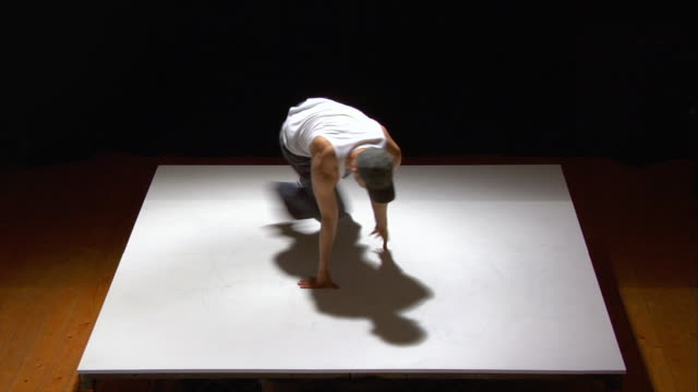 high angle medium shot breakdancer spinning on white floor - baggy jeans stock videos & royalty-free footage