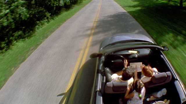 high angle medium shot car point of view family driving in convertible on country road / long island - auto convertibile video stock e b–roll