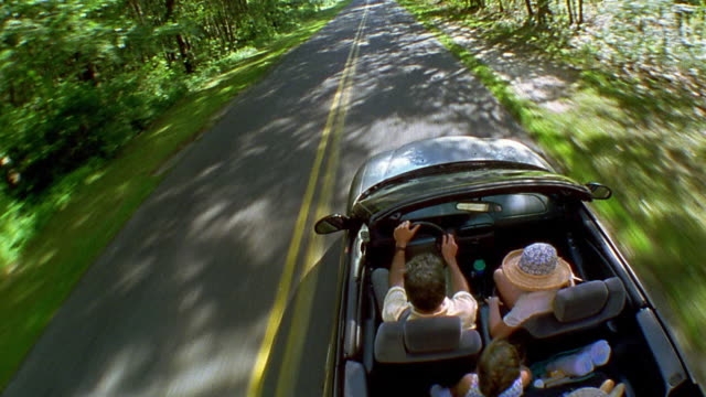 high angle medium shot car point of view family driving in convertible on country road - オープンカー点の映像素材/bロール