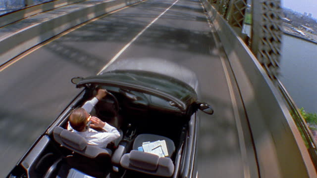 high angle medium shot car point of view man driving convertible on queensboro bridge and talking on cellular phone / nyc - cabrio stock-videos und b-roll-filmmaterial