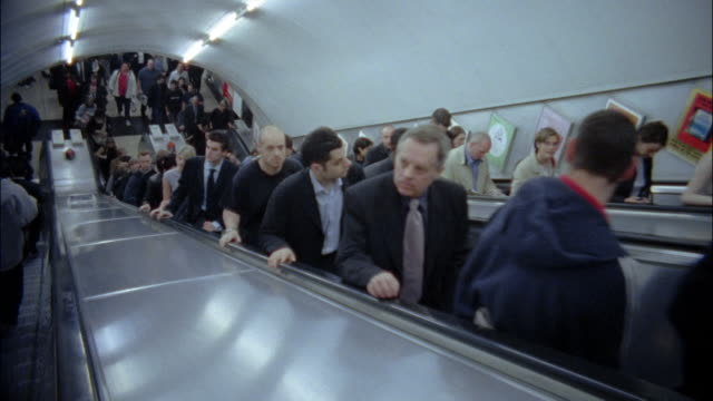 High angle medium shot commuters riding escalator up in Underground station / London, England