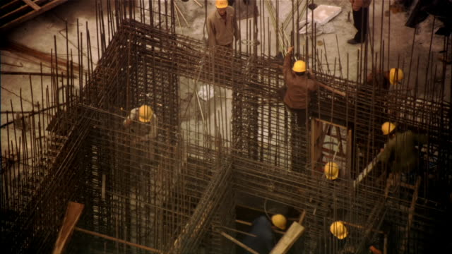 High angle medium shot contruction workers and frame of metal rods/ Beijing, China