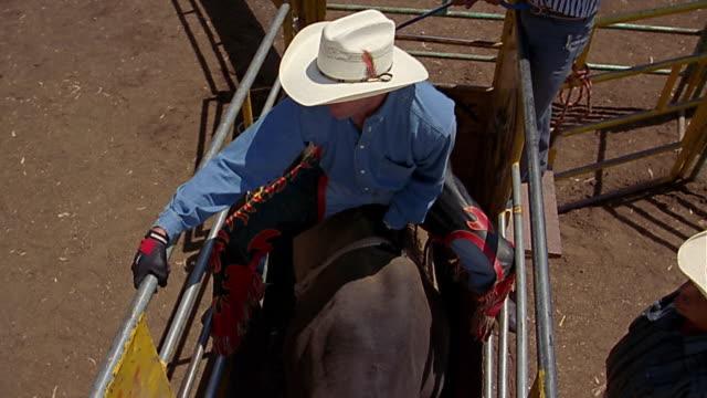 high angle medium shot crane shot coyboy getting on bull - rodeo stock videos & royalty-free footage