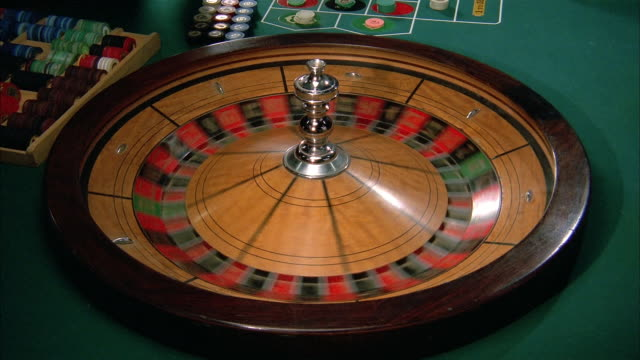 high angle medium shot croupier spinning roulette wheel on roulette table / california - roulette stock videos & royalty-free footage