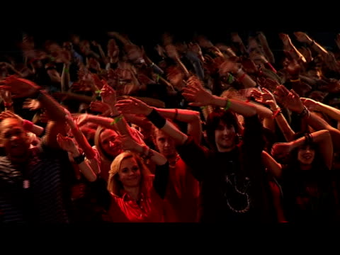 High angle medium shot crowd with arms above their heads and swaying in time at concert/ London, England