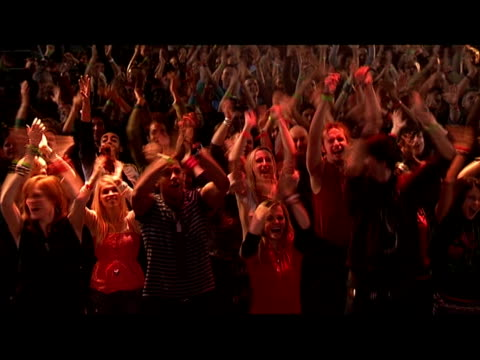 vidéos et rushes de high angle medium shot crowd with arms above their heads clapping at concert/ london, england - bras humain