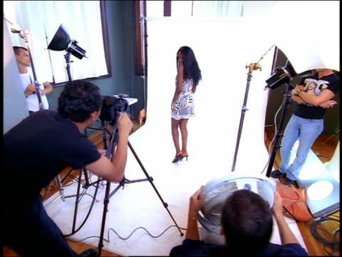 High angle medium shot dolly shot Black model posing in studio for photographer and fan operator