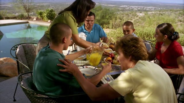 High angle medium shot dolly shot Hispanic family eating breakfast outdoors with pool and desert in background / Tucson, Arizona